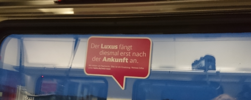 """Ein Aufkleber in einem Zug erklärt: """"Der Luxus fängt diesmal erst nach der Ankunft an"""""""