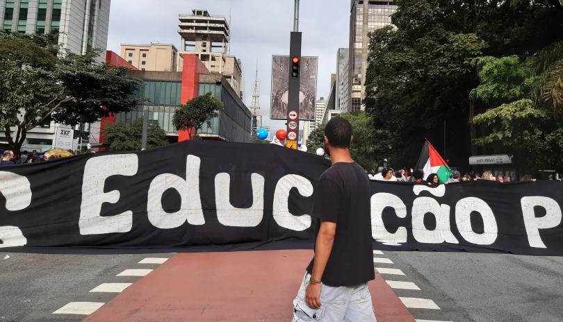 """Ein Mann geht bei einer Demonstration in São Paulo vor dem Wort """"Bildung"""" auf einem riesigen Spruchband vorbei"""